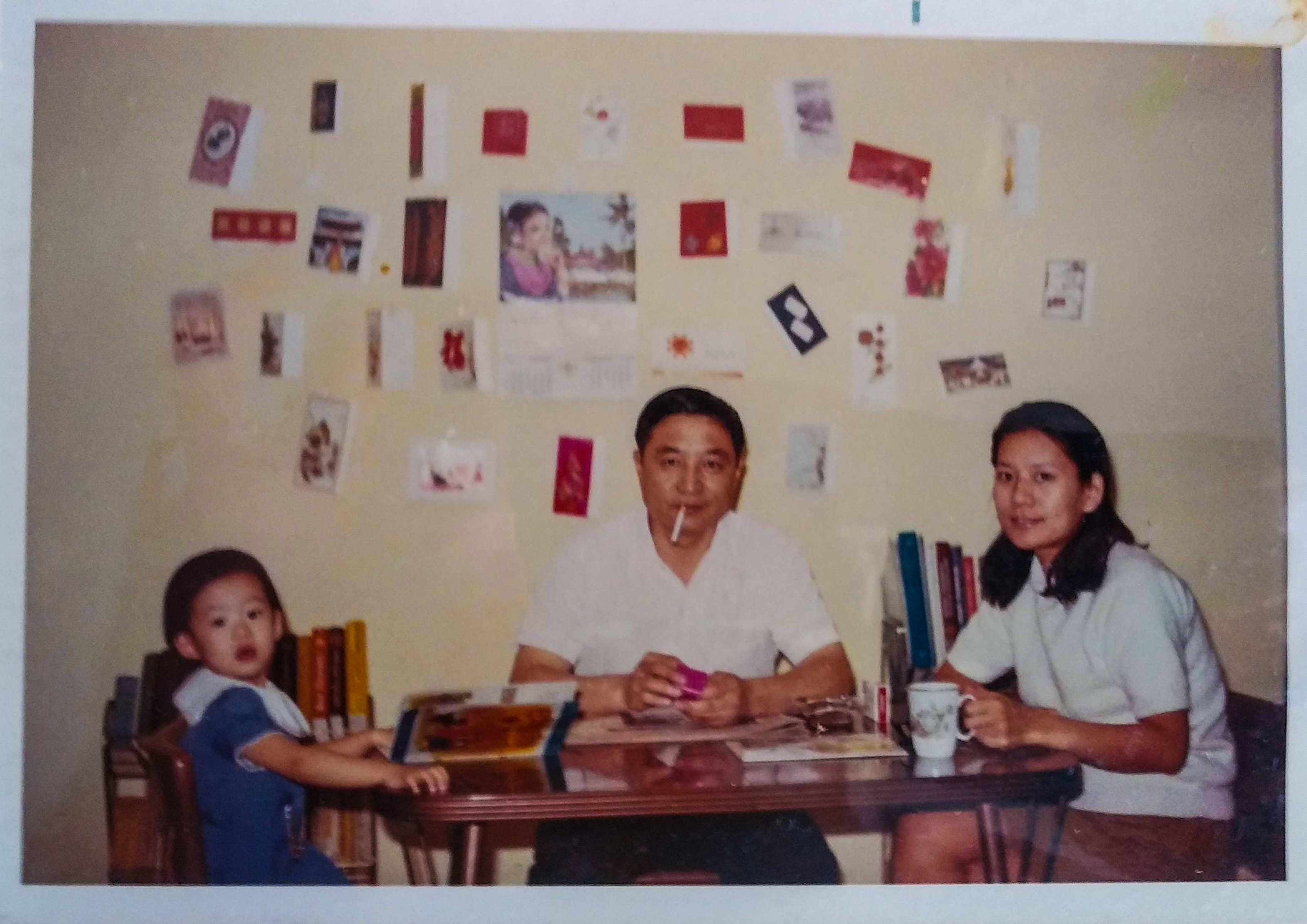 A woman (right) and a man (center) sit at a table at home with a baby (left). The man smokes a cigarette, the woman holds a white mug, and the baby holds open a children's book.