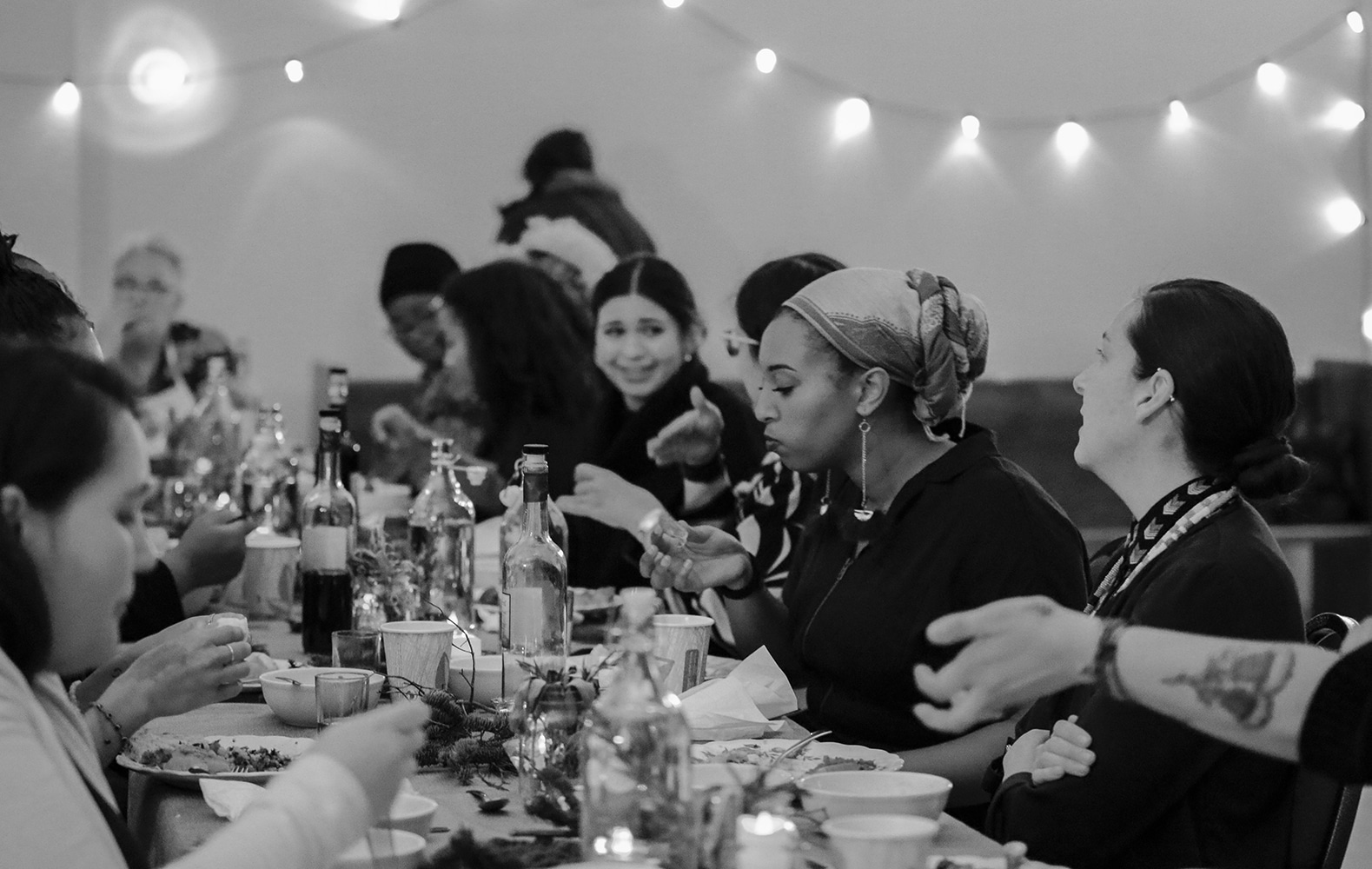 Black and white image of several women at a long table, eating, talking, laughing.