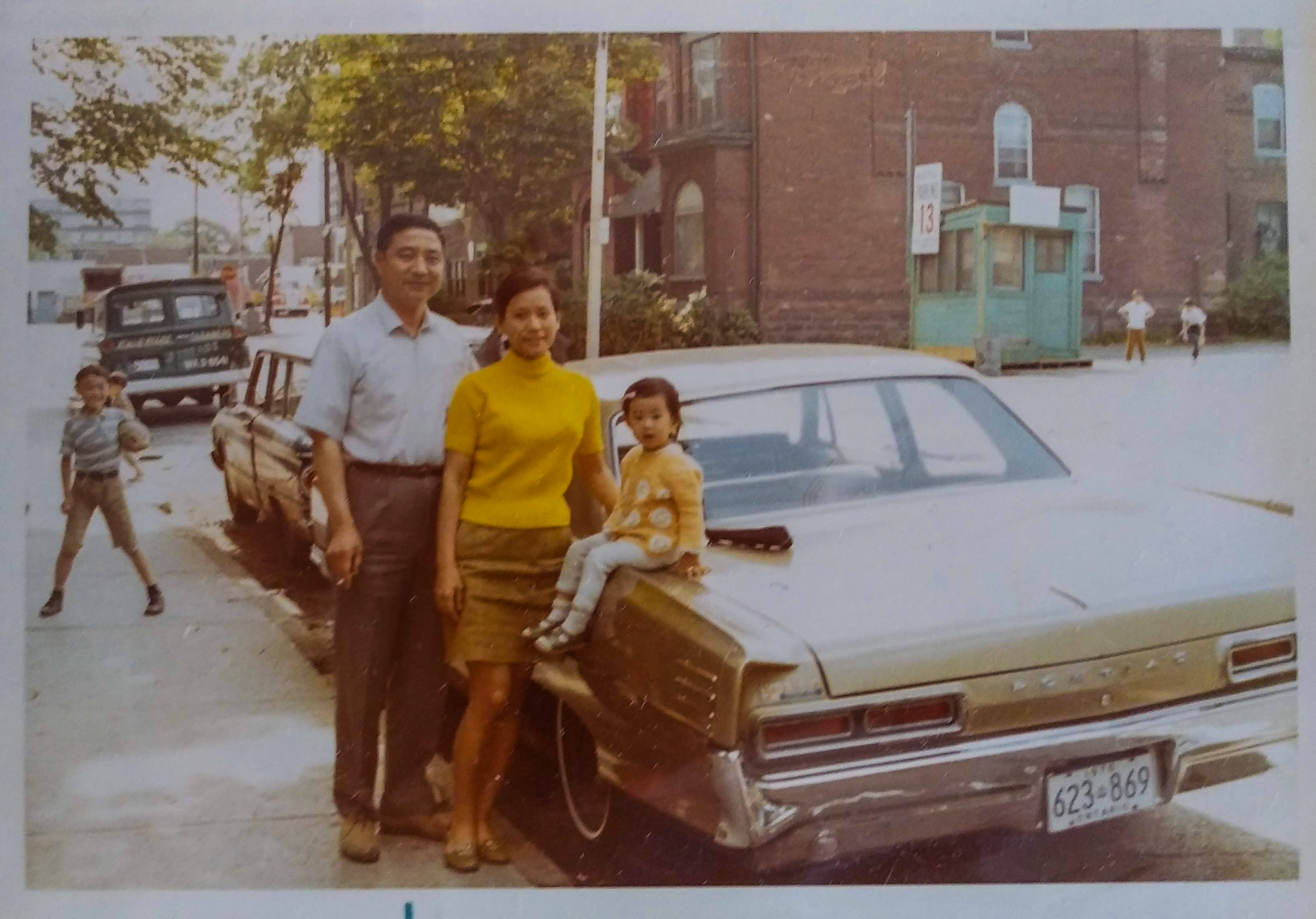 A man (left) and a woman (center) stand next to their brown Pontiac car. With them, their baby (the writer) is perched on the trunk of the car.
