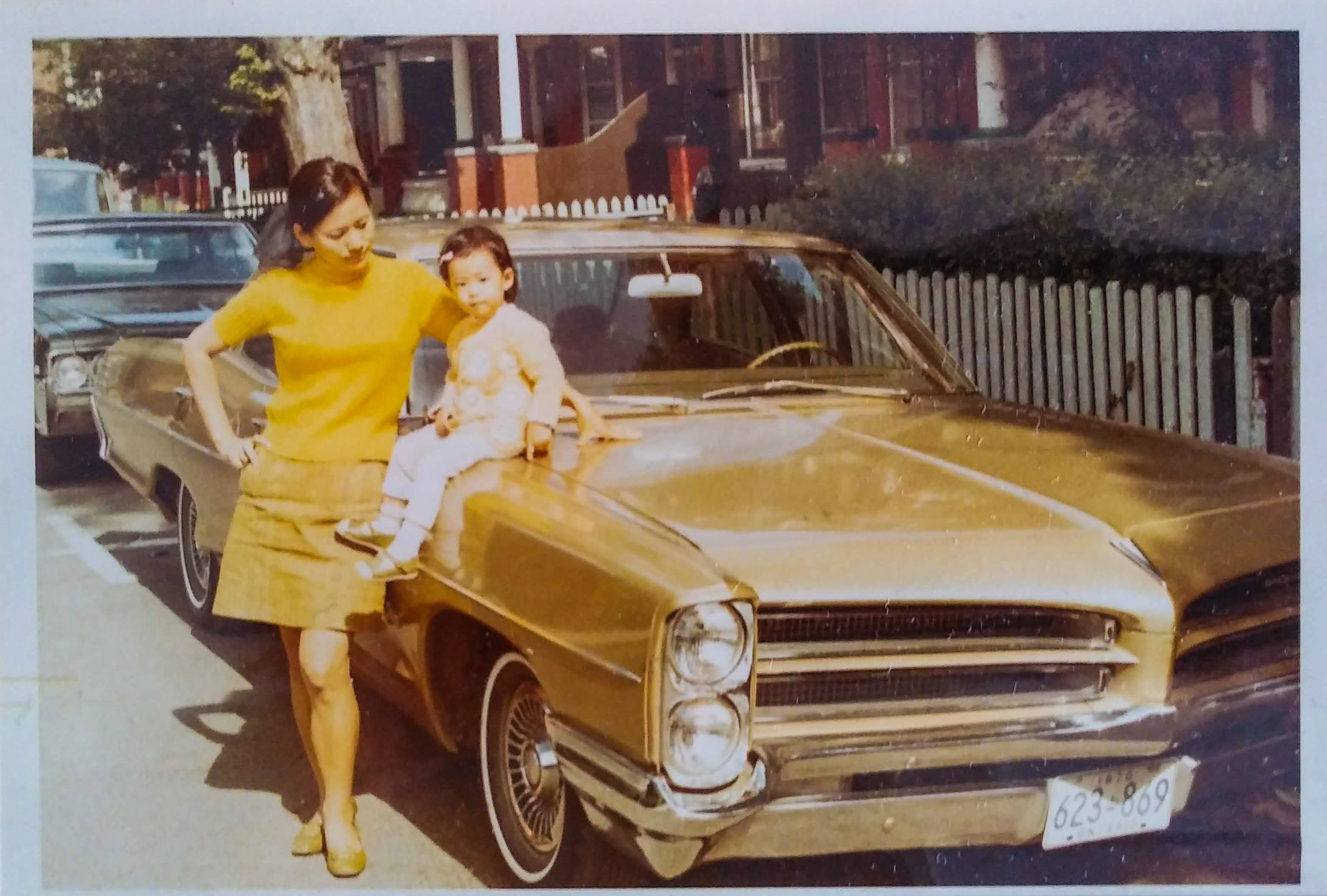 A woman (left) stands next to a brown Pontiac car. She looks down at her baby (the writer), who is perched on the trunk of the car.